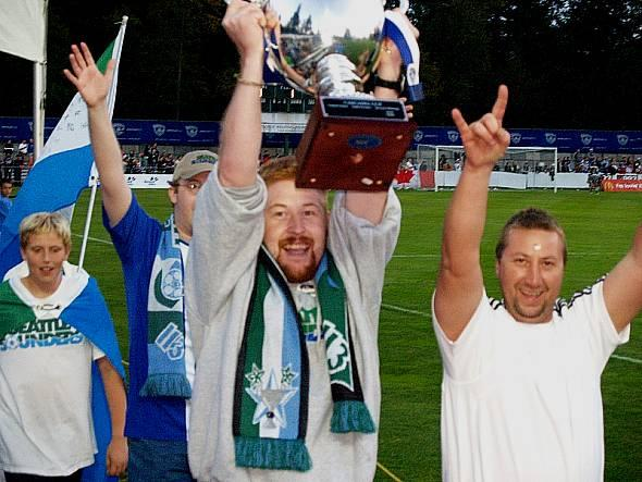 Seattle supporters get the Cup back in 2006 in what has become Cascadia tradition: one supporters group handing the trophy over to the new winners, who will hold it for the year. (Jenni Conner)