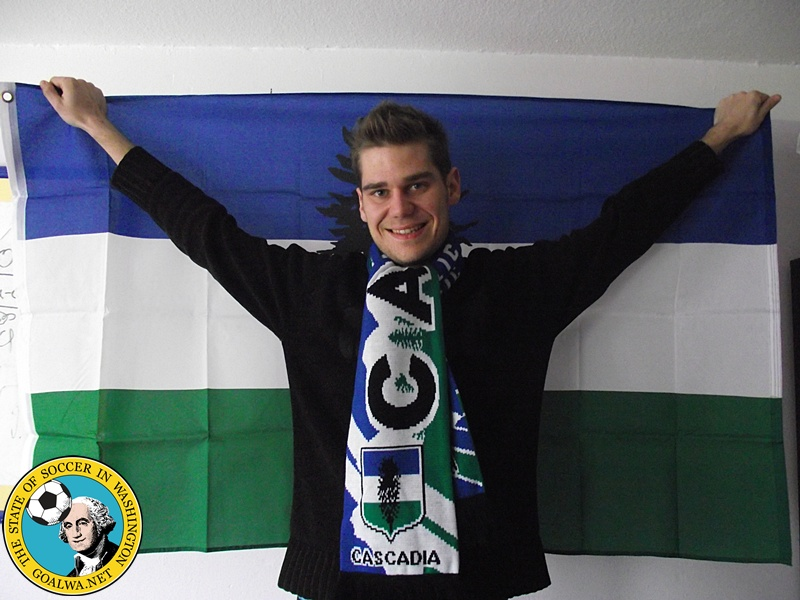 Sascha is a Cascadia supporter, displaying flag and scarf.