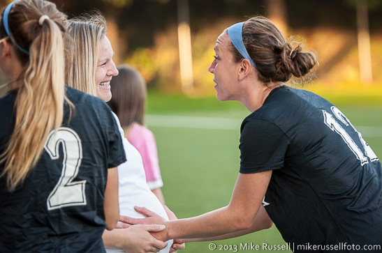 Alex Rodriguez on the sidelines at a Seattle Reign FC match this summer. Lauren Cheney greets her with a tummy hold. © Mike Russell | www.mikerussellfoto.com