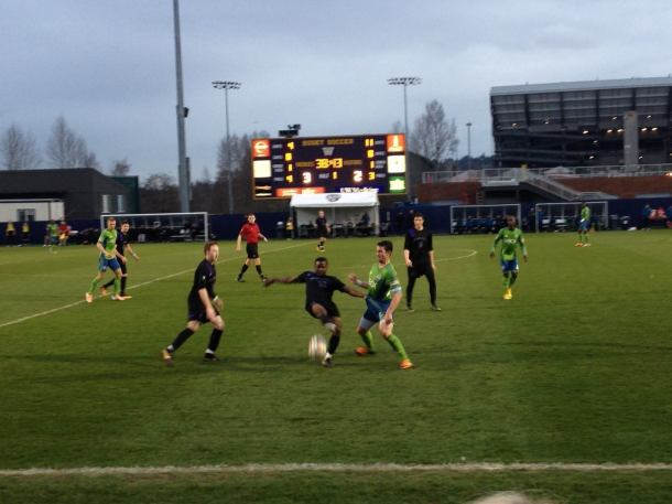 Jones in the middle against the Sounders' Zach Scott. (UW Facebook)
