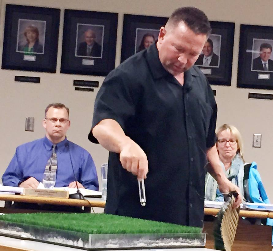 School Board photo: Field Turf rep. Donny Jones explains the surface to Wenatchee members.